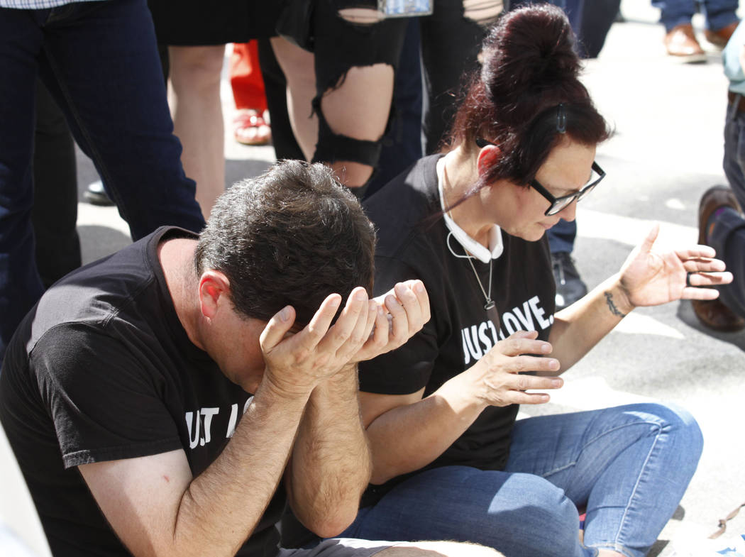 Scott Johnson of Las Vegas shows his emotion while Debbie Steffy of Las Vegas prays during a prayer vigil in remembrance of Oct. 1 shooting victims in front of Las Vegas City Hall in Las Vegas, Mo ...