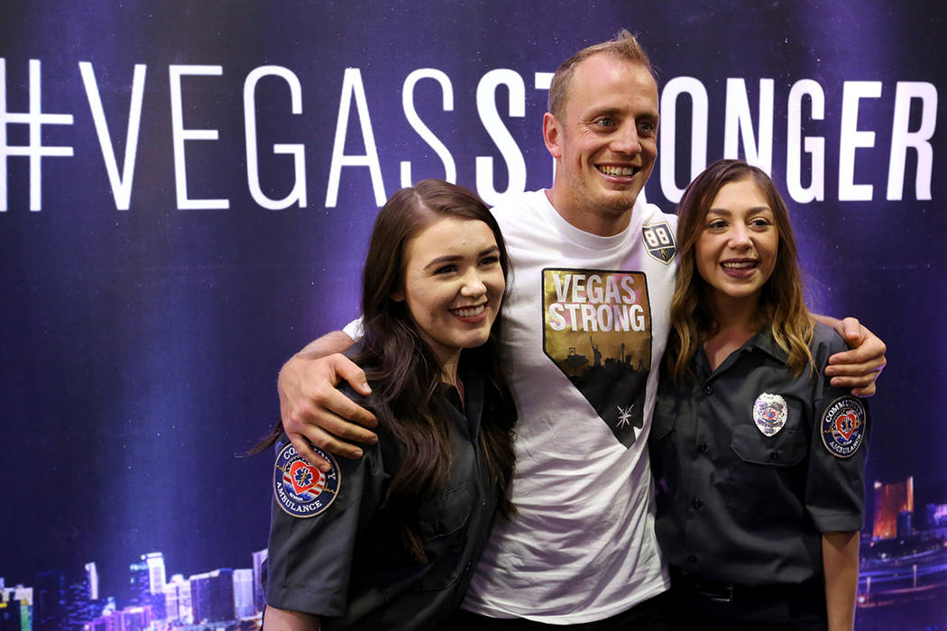 """Vegas Golden Knights player Nate Schmidt (88) poses with Randi Sloan, left, and Kaitlyn Rogers during a ceremony honoring members of Community Ambulance """"The 21"""" for their courage under fire, exce ..."""