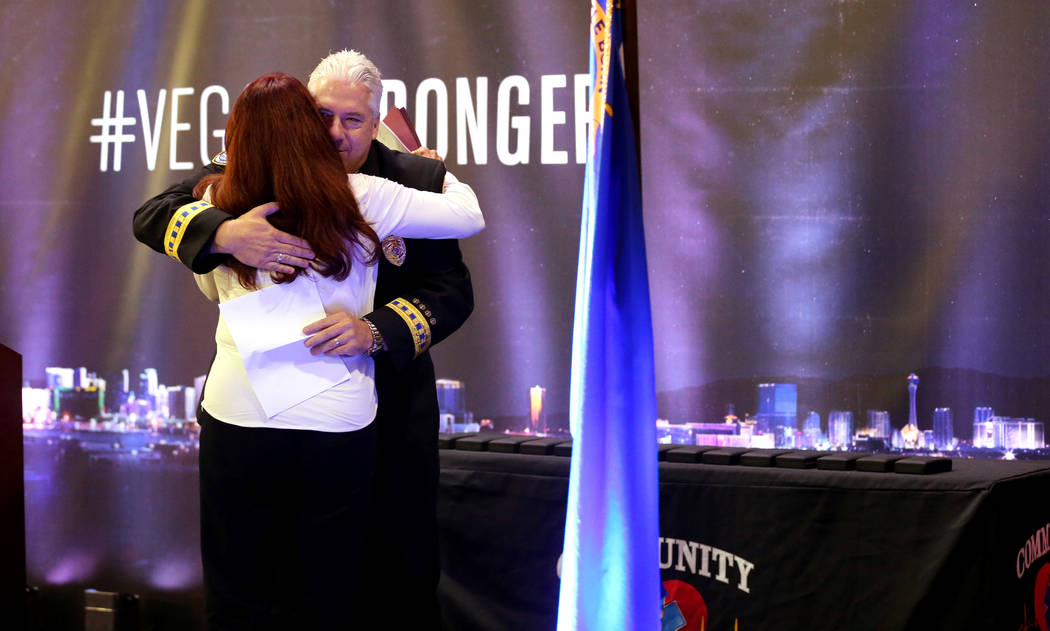 """CEO Robert Richardson hugs Henderson Mayor Debra March during a ceremony honoring members of Community Ambulance """"The 21,"""" for their courage under fire, exceptional care for patients and resilienc ..."""
