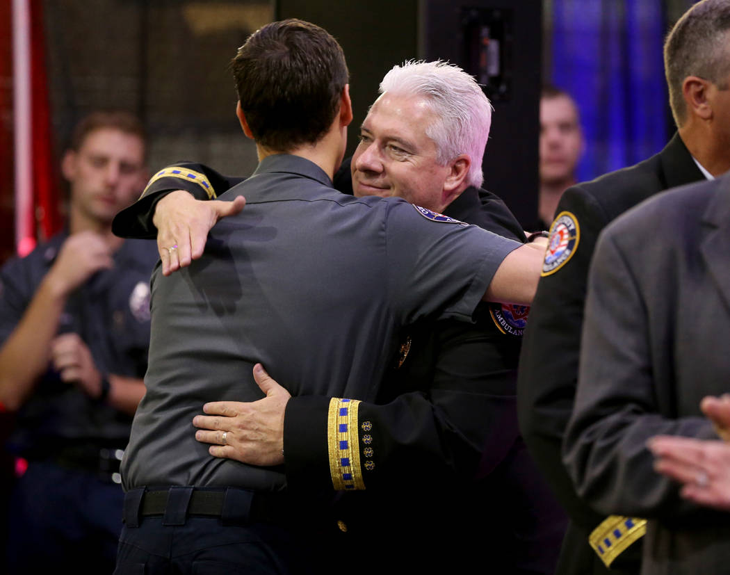 "CEO Robert Richardson hugs Jeff Yost, a member of Community Ambulance ""The 21,"" during a ceremony honoring their courage under fire, exceptional care for patients and resilience in the wake of the ..."