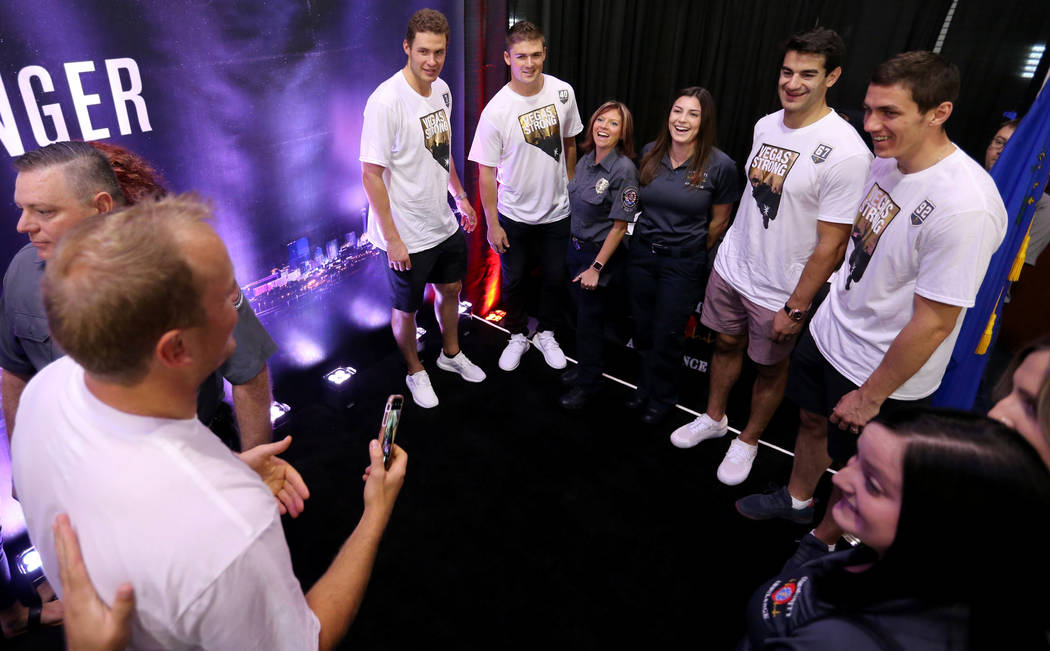 Vegas Golden Knights player Nate Schmidt, left, prepares to take a photo of, from left, Brayden McNabb (3), Ryan Carpenter (40), Mel Ondik, Carolyn Hensler, Max Pacioretty (67) and Tomas Nosek (9 ...