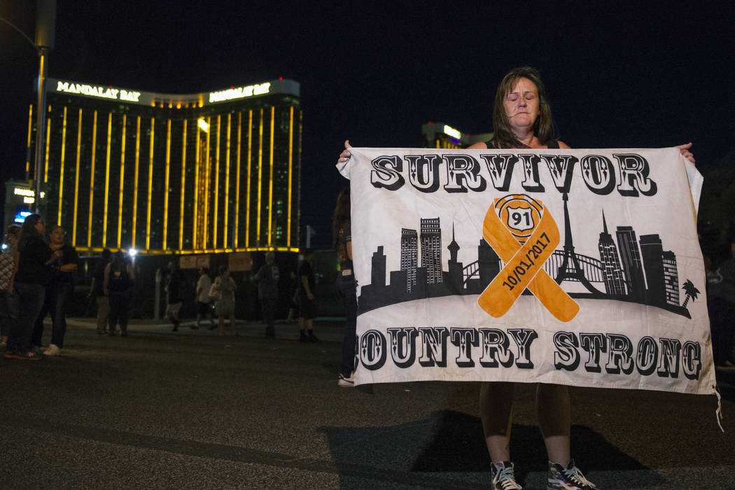 Roni Ryner holds up a survivor flag outside of the lot where the One October shooting happened a year ago in Las Vegas, Monday, Oct. 1, 2018. Caroline Brehman/Las Vegas Review-Journal