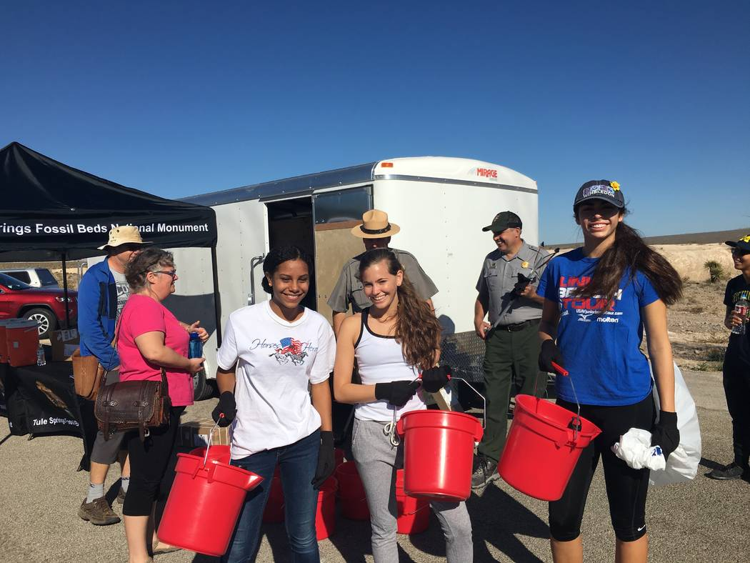 From left, Mirrorajah Metcalfe, 16, Tahoe Mack, 17, and Dani Mason, 17, take part in a cleanup event at Tule Springs Fossil Beds National. (Dawn Mack)