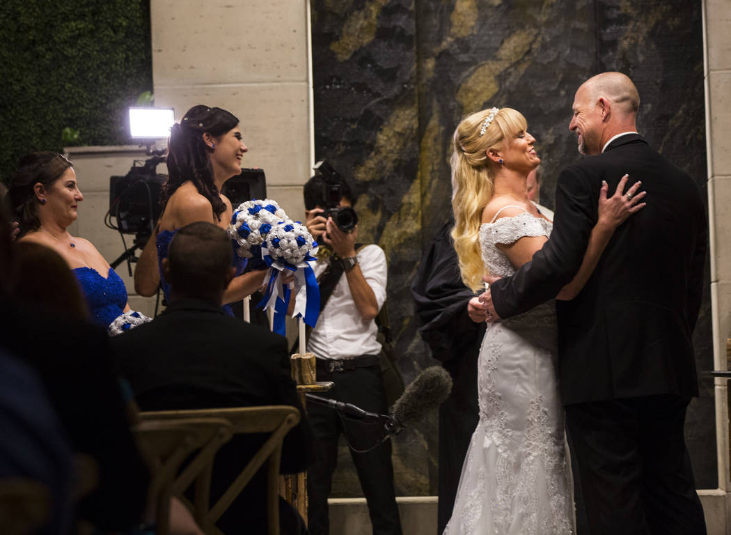 Oshia Collins-Waters, left, embraces Todd Wienke during their wedding ceremony at Chapel of the Flowers in Las Vegas on Monday, Oct. 1, 2018. Todd was shot three times as he shielded Oshia soon af ...