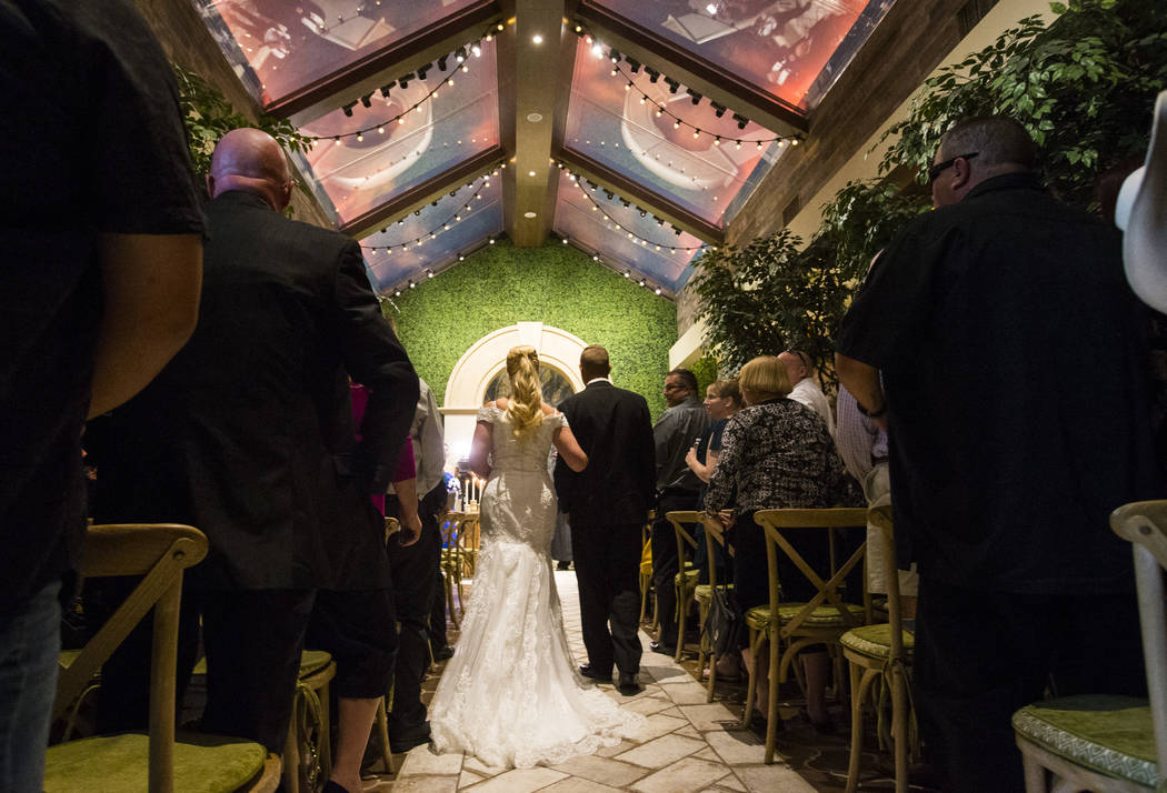 Bryce Cino, right, escorts his mother, Oshia Collins-Waters, down the aisle for her wedding ceremony with Todd Wienke at Chapel of the Flowers in Las Vegas on Monday, Oct. 1, 2018. Todd was shot t ...
