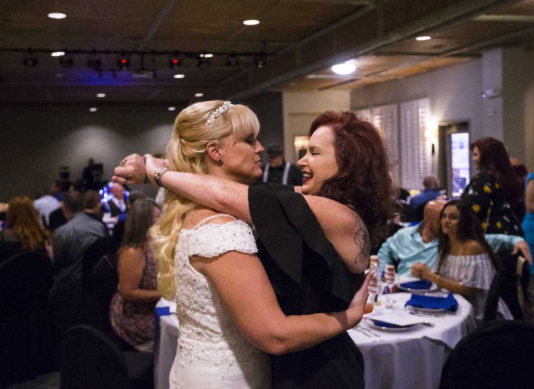 Oshia Wienke embraces friend and fellow Oct. 1 survivor Kimbur Presmyk of Las Vegas during their wedding reception at Tahiti Village in Las Vegas on Monday, Oct. 1, 2018. Todd was shot three times ...
