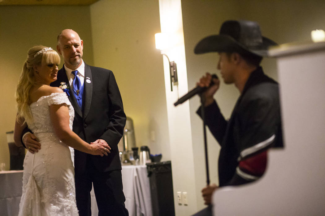 Todd and Oshia Wienke listen before a performance by country musician Sam Riddle during their wedding reception at Tahiti Village in Las Vegas on Monday, Oct. 1, 2018. Todd was shot three times as ...