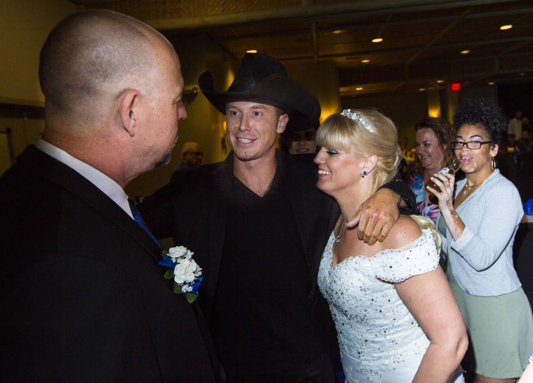 Country musician Sam Riddle, center, greets Todd and Oshia Wienke during their wedding reception at Tahiti Village in Las Vegas on Monday, Oct. 1, 2018. Todd was shot three times as he shielded Os ...