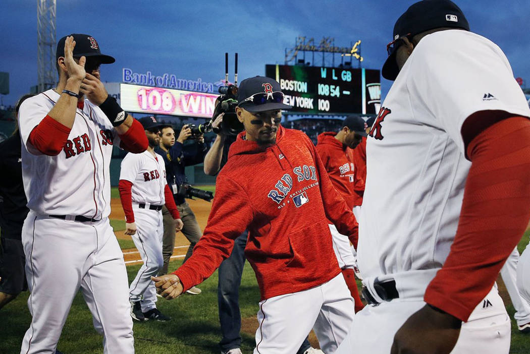 Boston Red Sox's Mookie Betts, center, celebrates with teammates after defeating the New York Yankees in the final game of the regular baseball season in Boston, Sunday, Sept. 30, 2018. (AP Photo/ ...