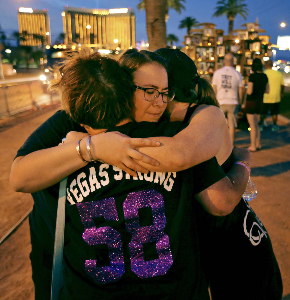 Liafaith Fischer, facing, hugs Cindy Loveless, and Jamie Steele at the Welcome to Fabulous Las Vegas sign on the one-year anniversary of the Oct. 1 Strip shooting. K.M. Cannon Las Vegas Review-Jou ...