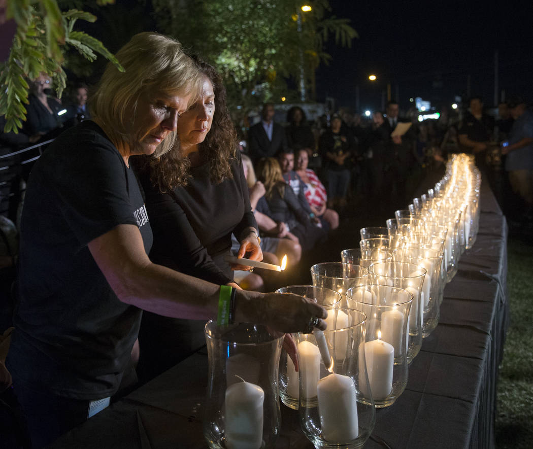 Esther Reincker, left, and Mauricia Baca light candles for the 58 victims of the Oct 1 shooting at 10:05 p.m., the exact time the shooting began last year, during a ceremony organized by the City ...
