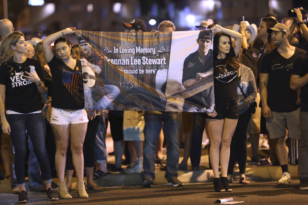 Cristina Armington, from left, Azjhree Lee and Lizzie Lee, all friends of Brennan Lee Stewart, who died in the Oct. 1 shooting, hold a banner in honor of Stewart outside Mandalay Bay hotel-casino ...