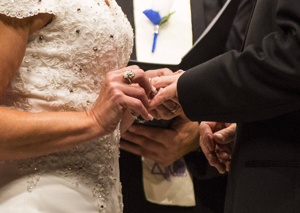 Oshia Collins-Waters, left, puts a ring on the finger of Todd Wienke during their wedding ceremony at Chapel of the Flowers in Las Vegas on Monday, Oct. 1, 2018. Todd was shot three times as he sh ...