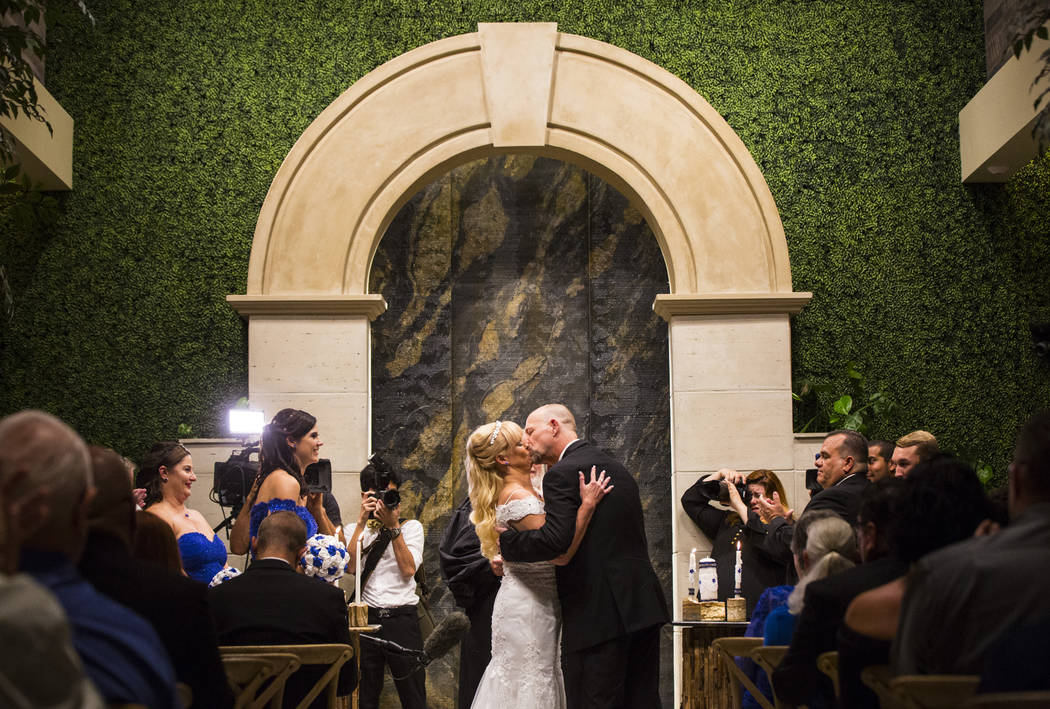 Oshia Collins-Waters, left, kisses Todd Wienke during their wedding ceremony at Chapel of the Flowers in Las Vegas on Monday, Oct. 1, 2018. Todd was shot three times as he shielded Oshia soon afte ...