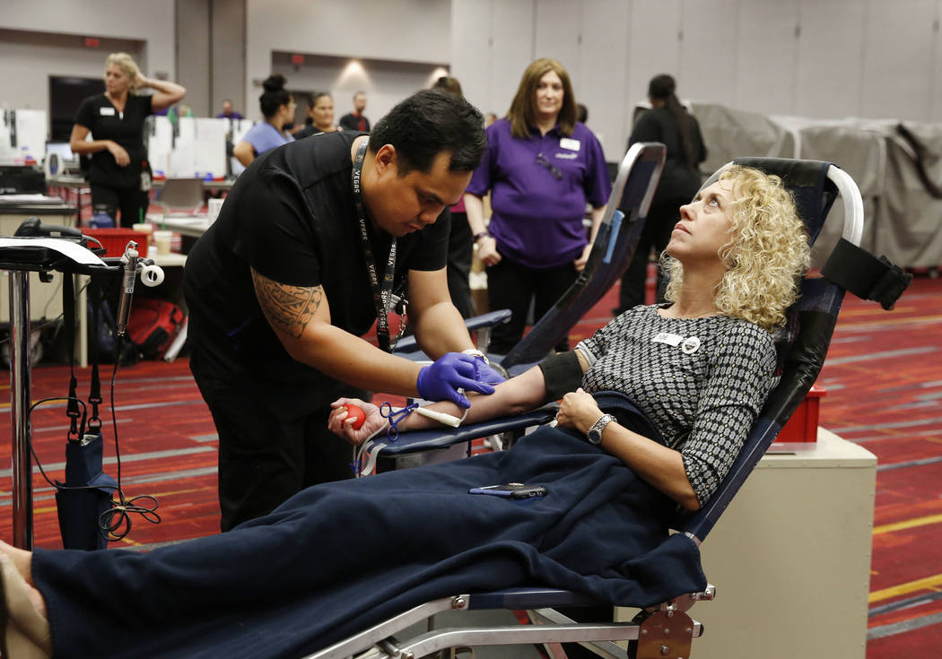 Ivan Puzon, donor care specialist, draws blood from Kelly Messing at the Las Vegas Convention Center on Monday, Oct. 1, 2018, during a blood drive to commemorate the Oct. 1 shooting. Bizuayehu Tes ...