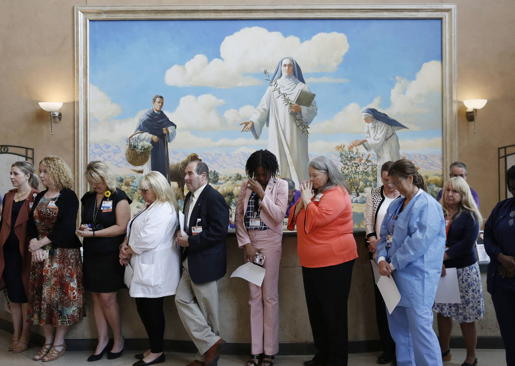 St. Rose Dominican Hospital employees pray during the dedication of a light sculpture, in commemoration of the Oct. 1 shooting, on Monday, Oct. 1, 2018, in Henderson. Bizuayehu Tesfaye/Las Vegas R ...