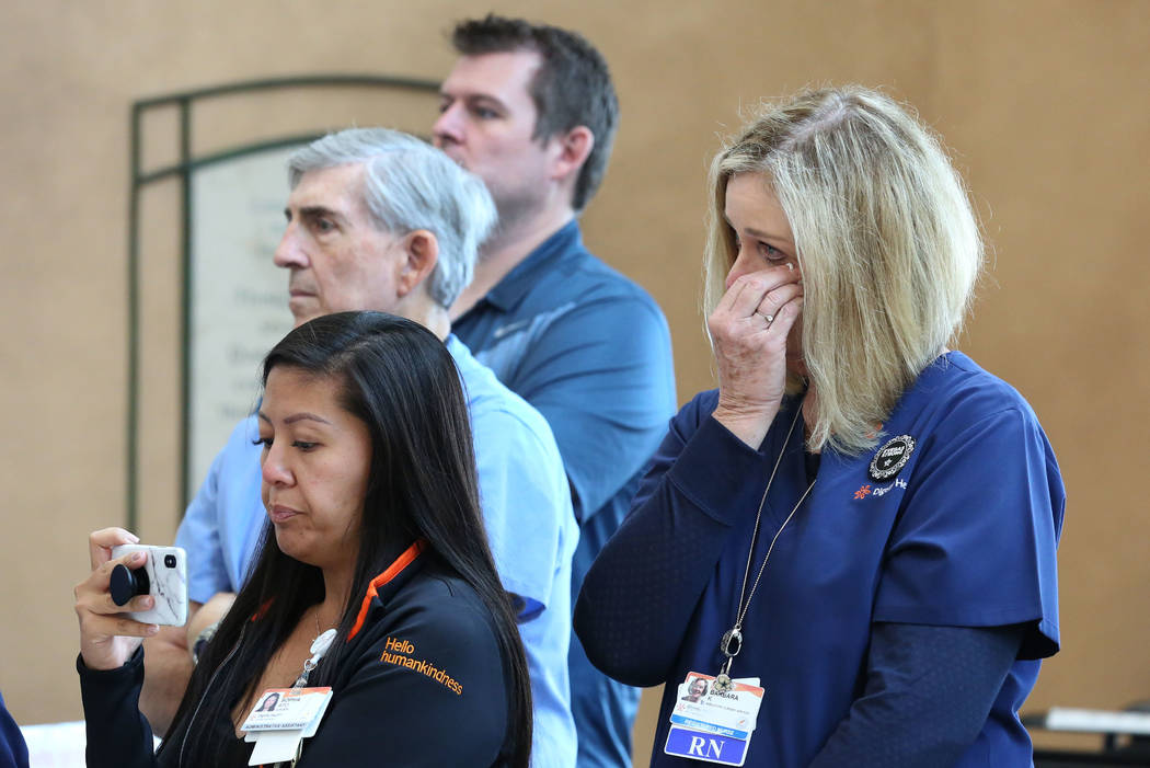 Barbara Kordestani, right, a register nurse at St. Rose Dominican Hospital, weeps during the dedication of a light sculpture, in commemoration of the Oct. 1 shooting, on Monday, Oct. 1, 2018, in H ...