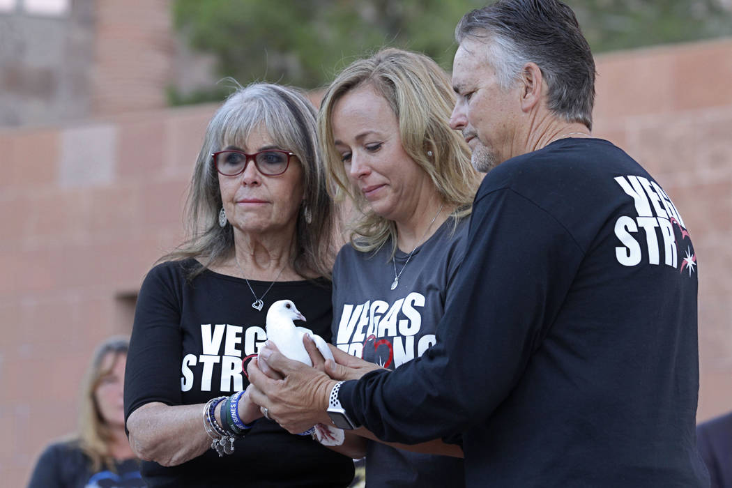Mynda Smith, sister of Route 91 victim Neysa Tonks, center, and her parents, Debbie and Chris Davis, are ready to release a dove during a 1 October sunrise remembrance ceremony at the Clark County ...