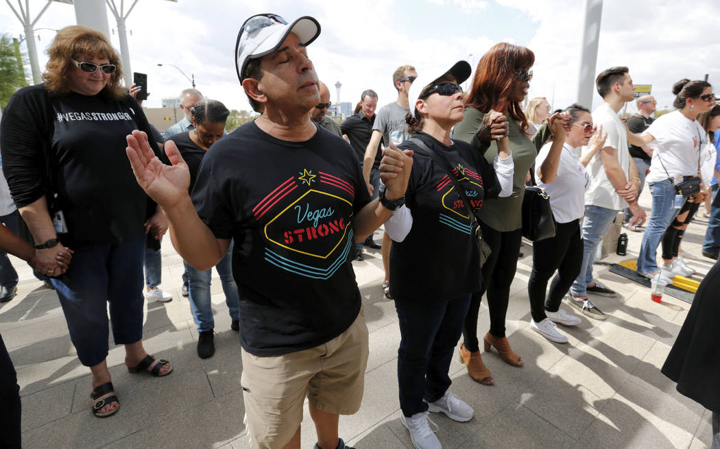 Attendees pray during a prayer vigil in remembrance of Oct. 1 shooting victims in front of Las Vegas City Hall in Las Vegas, Monday, Oct. 1, 2018. Chitose Suzuki Las Vegas Review-Journal @chitosephoto