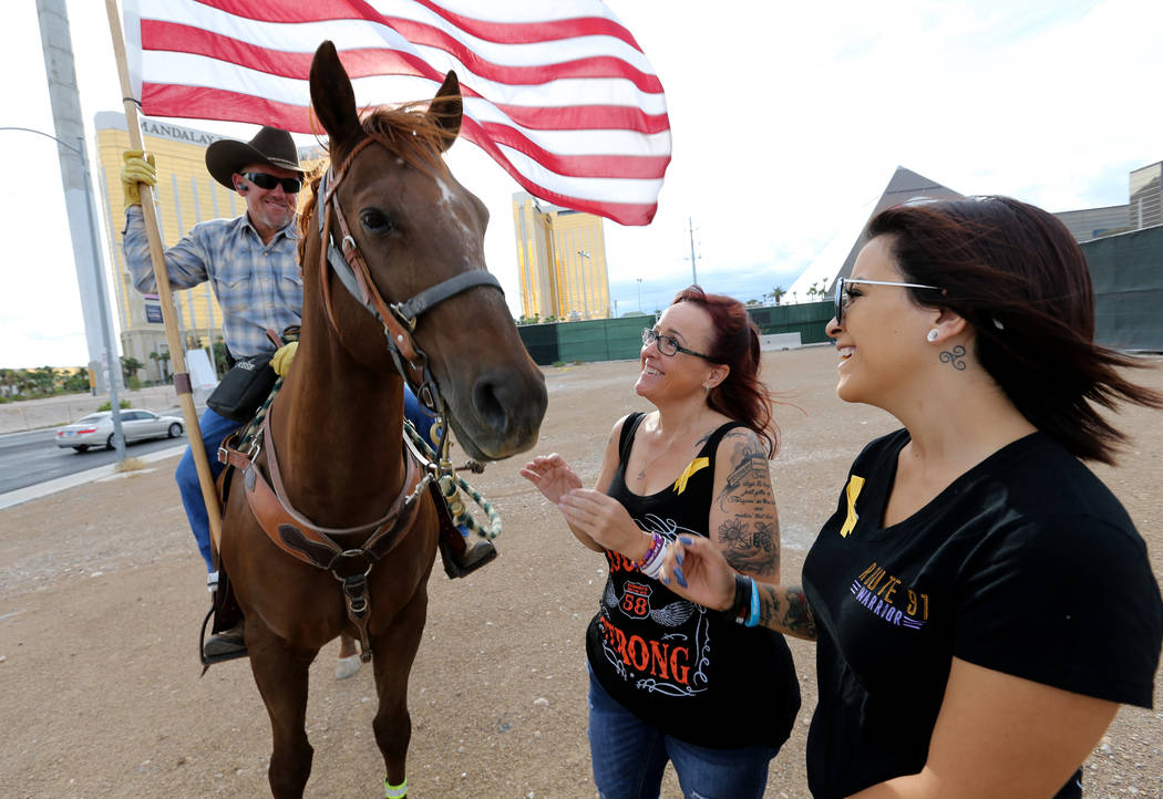 Cheryl Davis and her daughter Sydney of Las Vegas visit with Rafael Sarabia of Mountain Springs on the corner of Giles Street and Mandalay Bay Road near the Route 91 Harvest Festival site Monday, ...