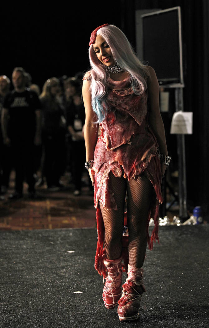 """FILE - In this Sept. 12, 2010 file photo, singer Lady Gaga walks backstage wearing a dress made of meat after accepting the award for video of the year for """"Bad Romance"""" at the MTV Video ..."""