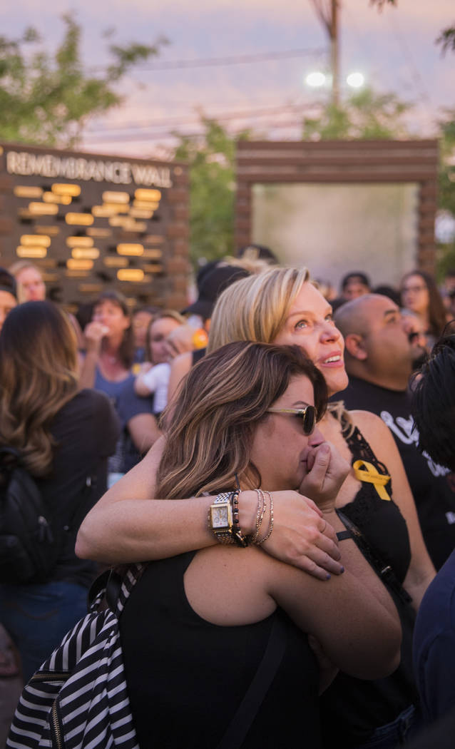 Melisa Barret, left, and Nina Siglin wipe away tears during the dedication of the new remembrance wall honoring victims of Oct 1 hosted by the City of Las Vegas in conjunction with Get Outdoors Ne ...