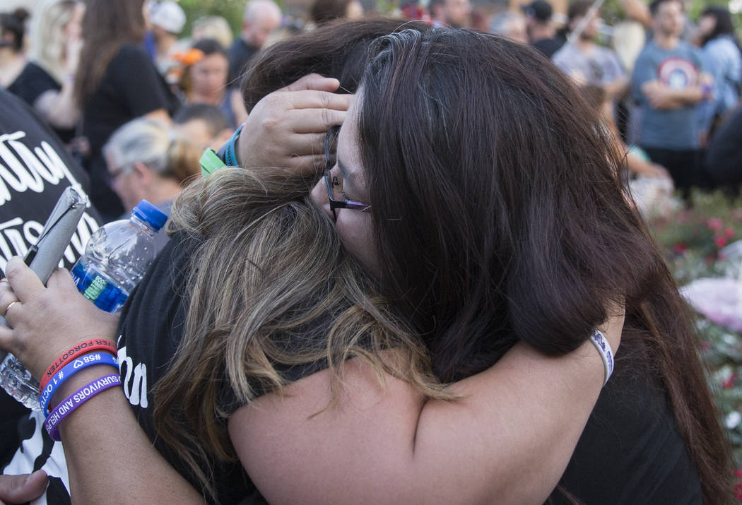 Jennie Redondo-Rosales, right, hugs Cindy Holguin during the dedication of the new remembrance wall honoring victims of Oct 1 hosted by the City of Las Vegas in conjunction with Get Outdoors Nevad ...