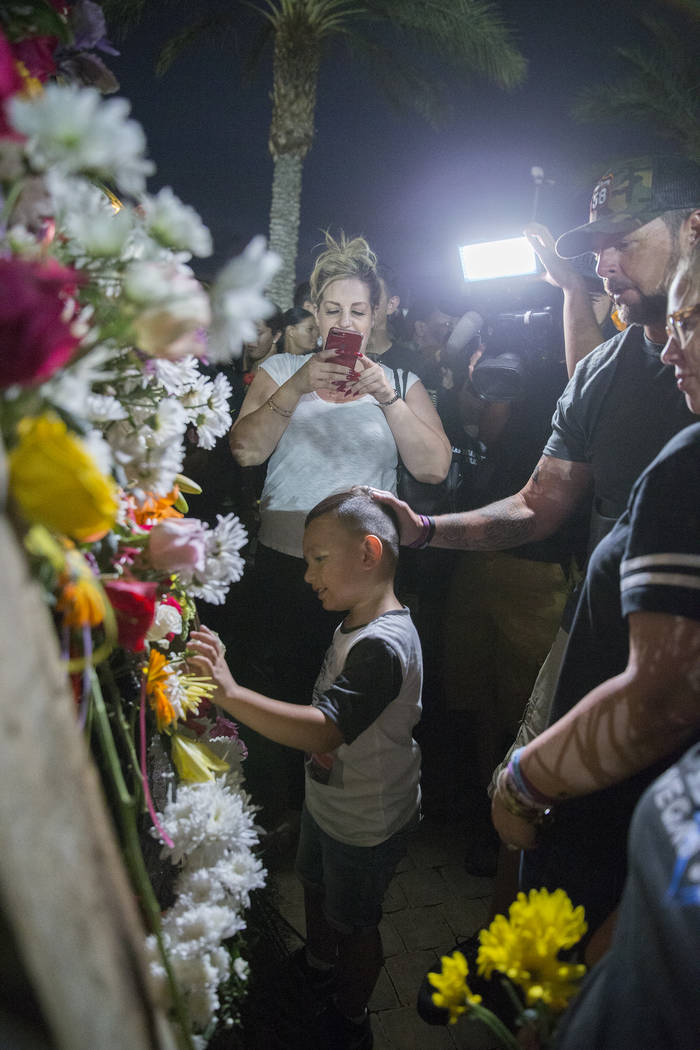 Flowers are hung during the dedication of the new remembrance wall honoring victims of Oct 1 hosted by the City of Las Vegas in conjunction with Get Outdoors Nevada on Monday, Oct. 1, 2018, at the ...