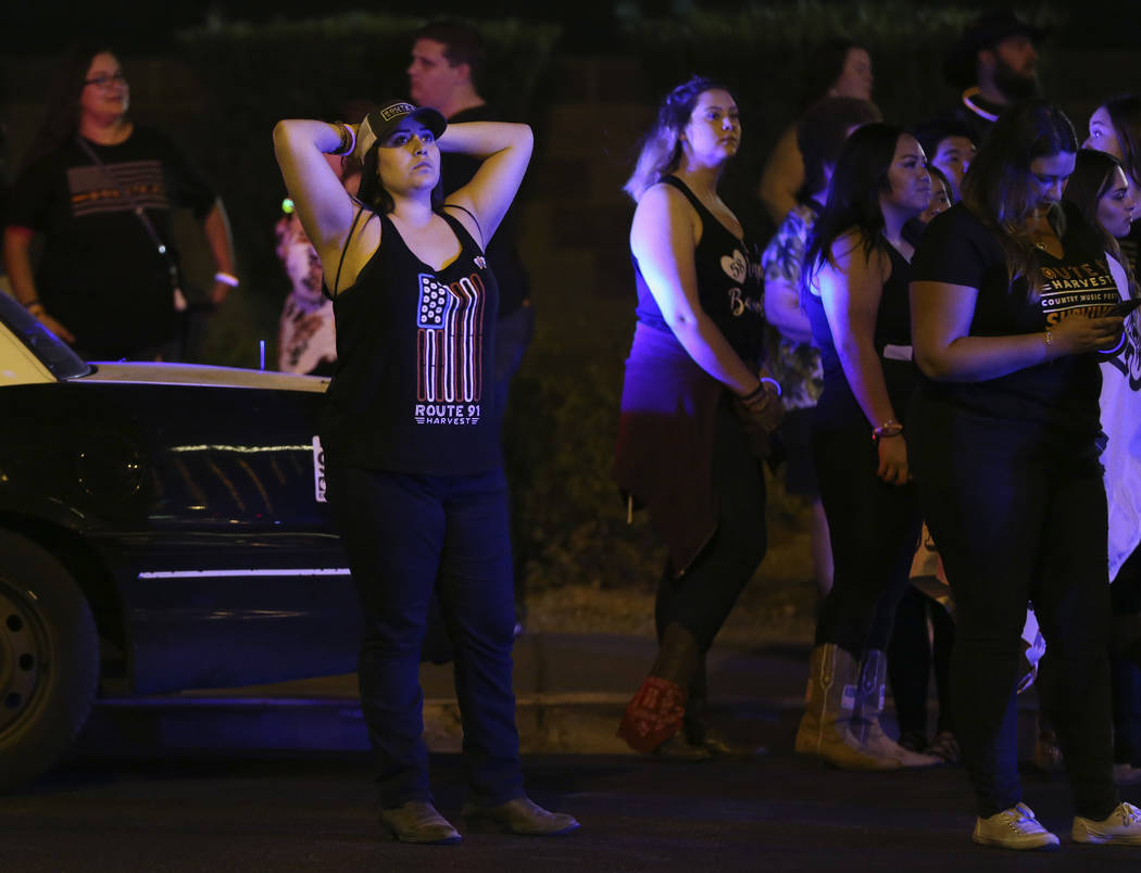 Route 91 Harvest festival survivor Sabrina Esparza, of California, waits for the lights to dim at Mandalay Bay hotel-casino on the anniversary of the 1 October shooting in Las Vegas, Monday, Oct. ...