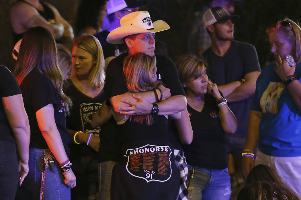 Route 91 Harvest festival survivor Kevin Williams hugs friend and fellow survivor, Karen Smith, of California, as they wait for the lights to dim at Mandalay Bay on Monday, Oct. 1, 2018, one year ...