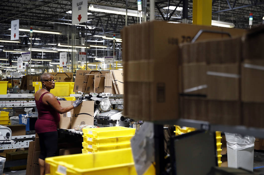 Cynthia Richburg prepares a product for shipment at an Amazon fulfillment center in Baltimore, Aug. 3, 2017. Amazon is boosting its minimum wage for all U.S. workers to $15 per hour starting next ...