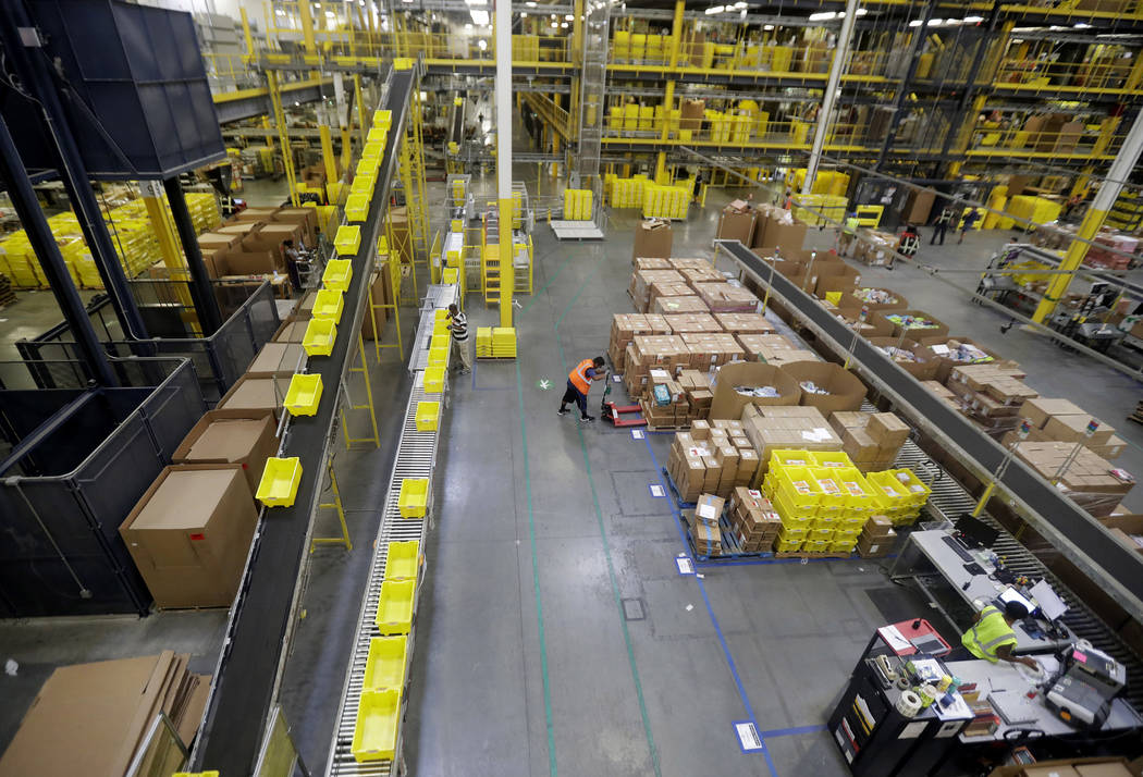 Employees work at the Amazon Fulfillment center in Robbinsville Township, N.J., Aug. 1, 2017. Amazon is boosting its minimum wage for all U.S. workers to $15 per hour starting next month. (Julio C ...