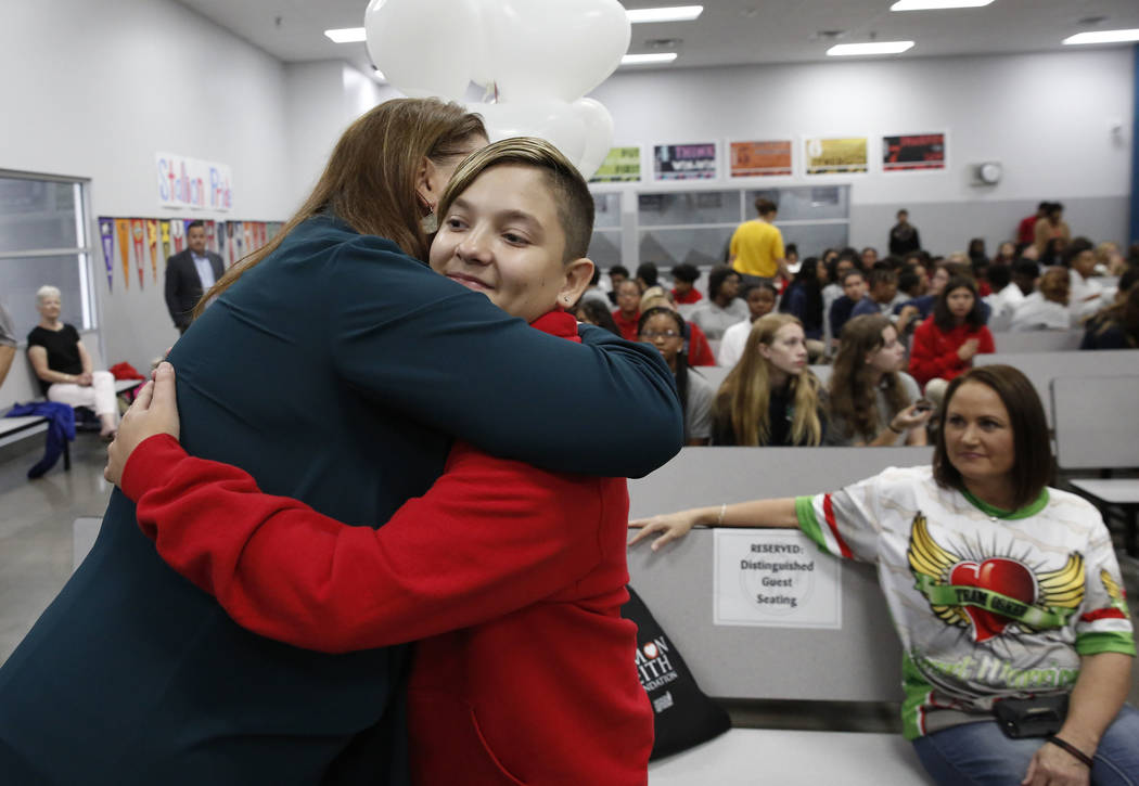 Osker Gamboa, who received a heart transplant on April 30, 2017, hugs his principal, Kenyan Martinez, after being honored by one of the longest living organ transplant recipient, Simon Keith, foun ...