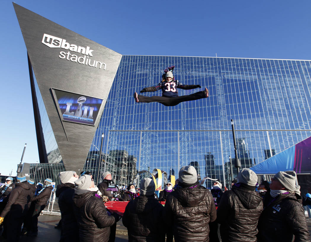 St. Paul Bouncing Team's Cassie Lukin wears a New England Patriots jersey while doing the splits in the air prior to Super Bowl LII at the US Bank Stadium in Minneapolis, Minn., Sunday, Feb. 4, 2018.