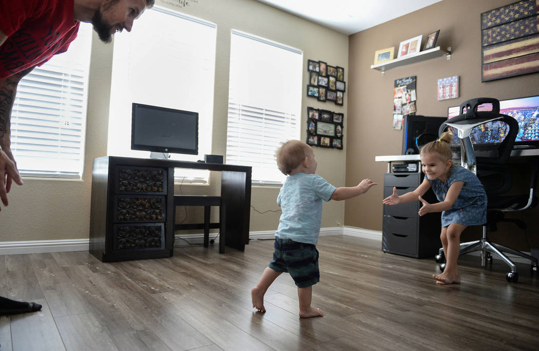 Travis Matheson, left, watches as his son, Wyatt, 1, walk over to his daughter, Lylah, 4, in their home in Las Vegas, Sunday, Sept. 30, 2018. Caroline Brehman/Las Vegas Review-Journal