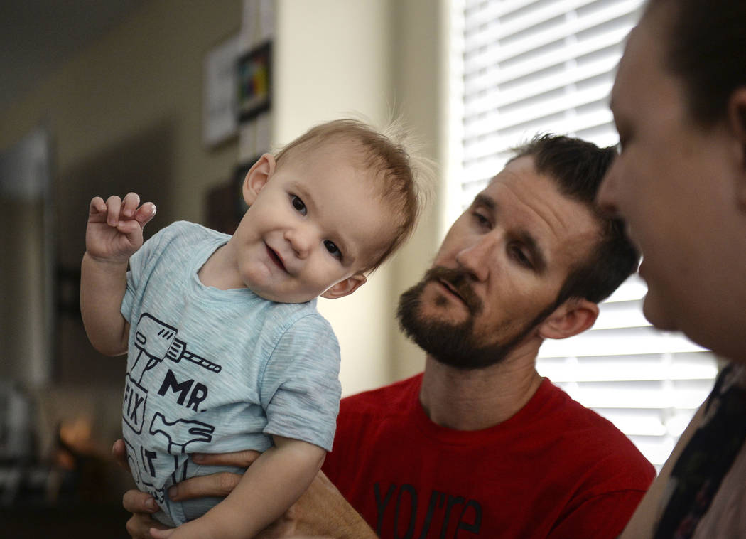 Wyatt Matheson, 1, stands on the lap of his father, Travis Matheson, in their home in Las Vegas, Sunday, Sept. 30, 2018. Caroline Brehman/Las Vegas Review-Journal