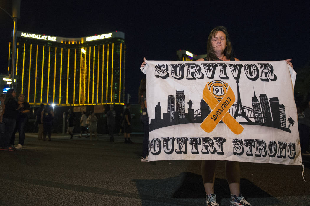 Roni Ryner holds up a survivor flag outside of the lot where the 1 October shooting happened a year ago in Las Vegas, Monday, Oct. 1, 2018. Caroline Brehman/Las Vegas Review-Journal