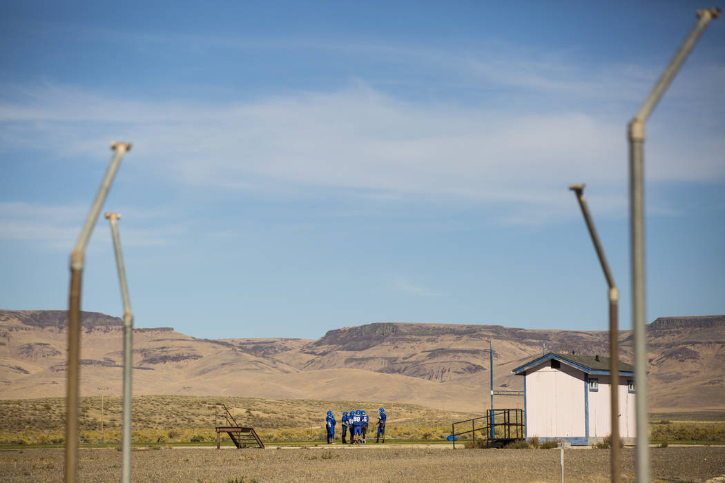 Football players gather for practice at McDermitt High School in McDermitt on Tuesday, Sept. 25, 2018. The restroom, right, was built by the school's shop class, one of few amenities on the field. ...