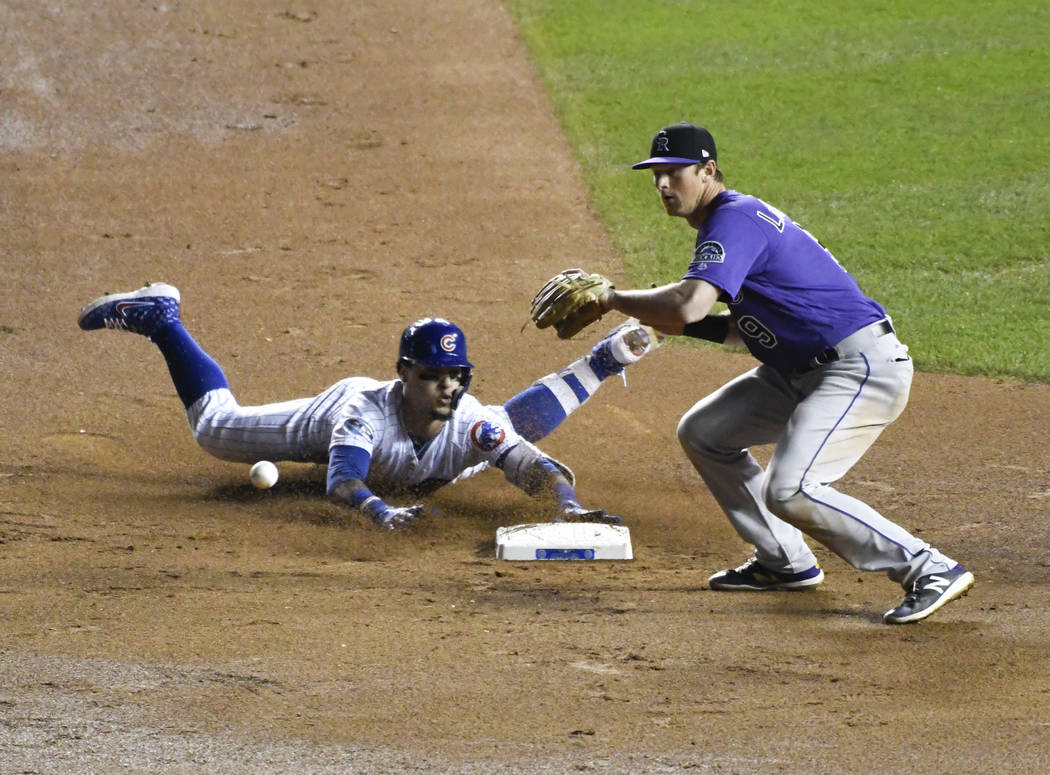 Chicago Cubs' Javier Baez, left, slides into second base safely as he hit a one-run double as Colorado Rockies second baseman DJ LeMahieu (9) makes a late tag during the eighth inning of the Natio ...