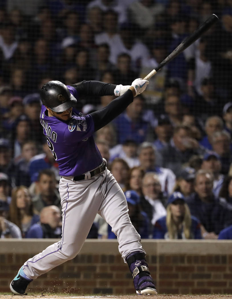 Colorado Rockies' Nolan Arenado hits a sacrifice fly against the Chicago Cubs during the first inning of the National League wild-card playoff baseball game Tuesday, Oct. 2, 2018, in Chicago. (AP ...