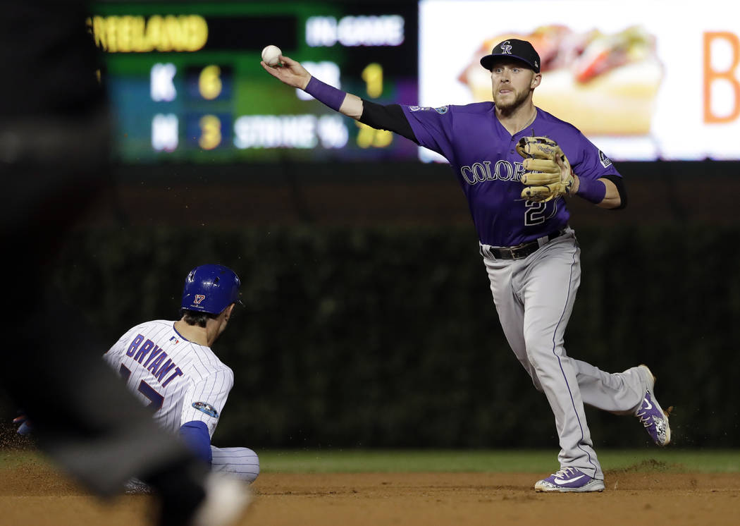 Colorado Rockies shortstop Trevor Story, right, throws out Chicago Cubs' Anthony Rizzo at first after forcing out Kris Bryant at second during the sixth inning of the National League wild-card pla ...