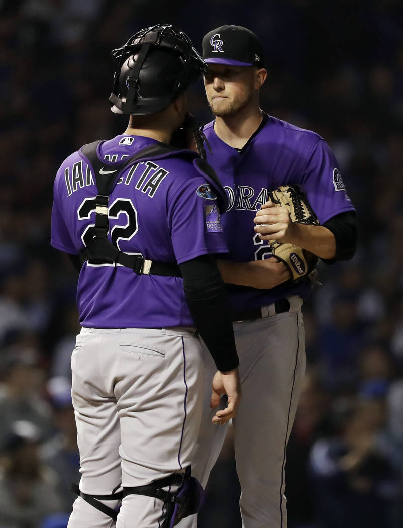 Colorado Rockies starting pitcher Kyle Freeland, right, talks with catcher Chris Iannetta during the sixth inning of the National League wild-card playoff baseball game against the Chicago Cubs, T ...