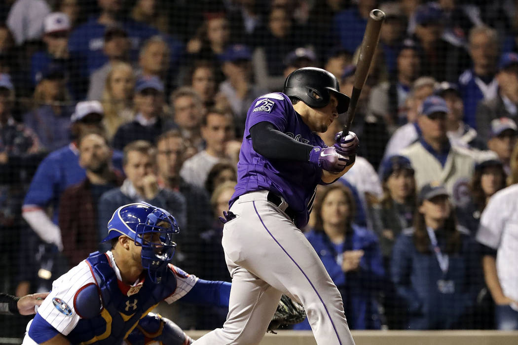 Colorado Rockies' Tony Wolters hits a one-run single against the Chicago Cubs during the 13th inning of the National League wild-card playoff baseball game Tuesday, Oct. 2, 2018, in Chicago. (AP P ...