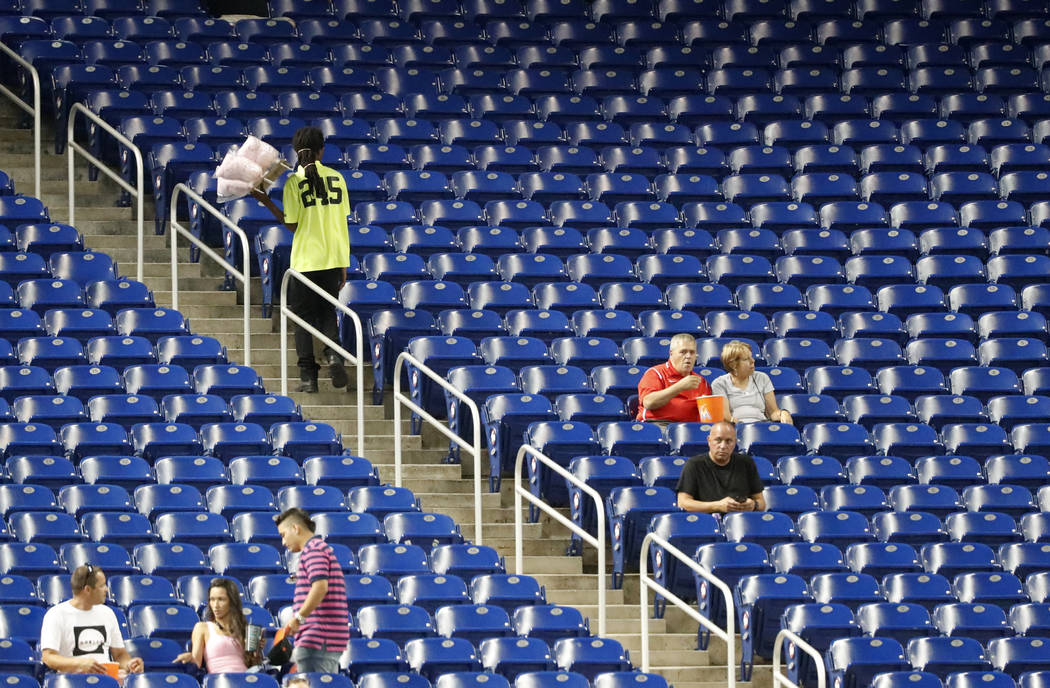 A vender walks past empty seats during the third inning of a baseball game between the Miami Marlins and the Washington Nationals, in Miami on Sept. 17, 201. Major League Baseball's attendance dro ...