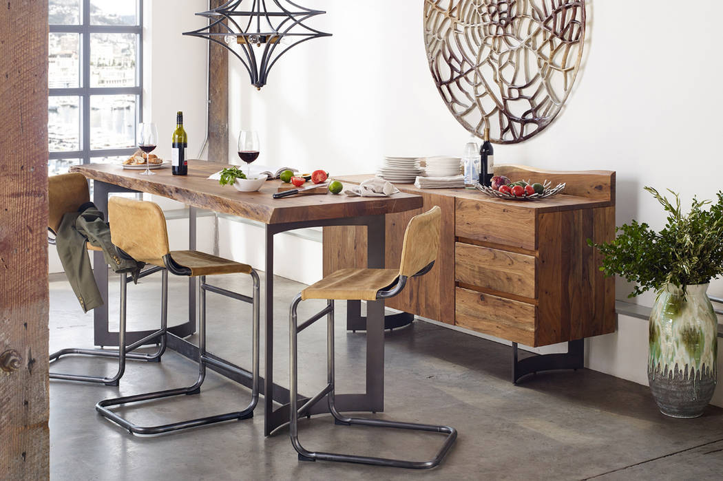 True bohemian style mixes and matches multiple styles. An ornate metal wall hanging complements the simple lines of wood and metal dining set. (Boho Furniture)