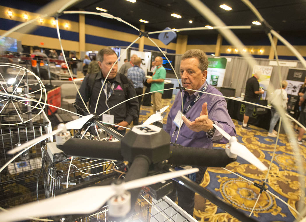 R4 Robotics Inc. president Karl Sachs, right, demos his R4 Roller drone, developed with a lined rolling cage, to attendee Larry Pruitt during the third annual Commercial UAV Expo at the Westgate i ...