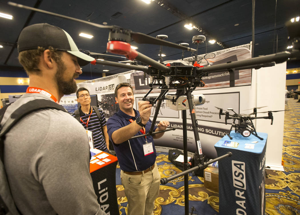 Daniel Hubert, right, of LiDAR USA demos the Matrice 201 LiDAR modular drone to attendees Troy Tetsuka, center, and Paul Fitzgerald during the third annual Commercial UAV Expo at the Westgate in L ...