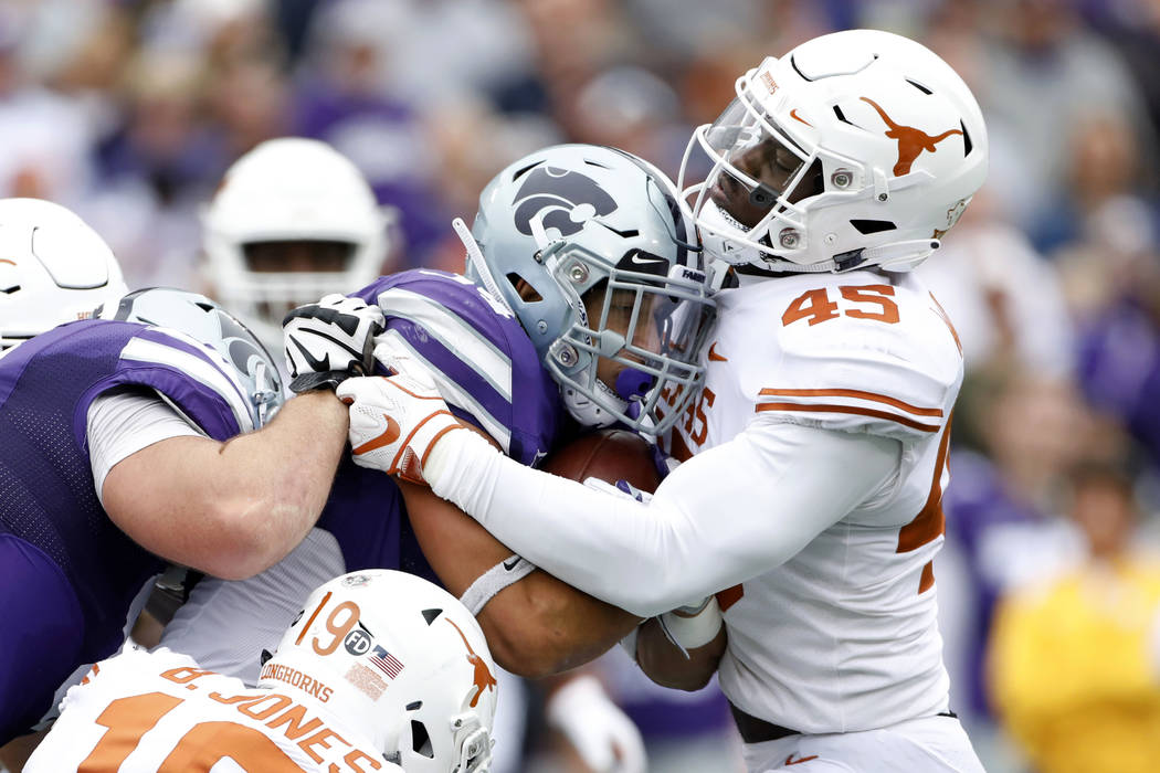 Kansas State running back Alex Barnes (34) is stopped at the line of scrimmage by Texas linebacker Anthony Wheeler (45) during the first quarter of a college football game in Manhattan, Kan., Satu ...