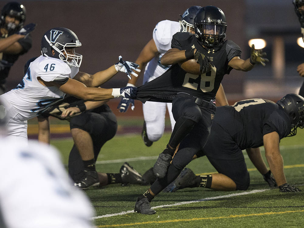 Valor Christian (Colorado) senior Darius Wayne (46) brings down Faith Lutheran running back Julian Rohan (28) during the first half of varsity football game at Faith Lutheran High School in Las Ve ...