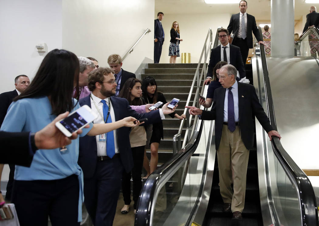 Senate Judiciary Committee Chairman Chuck Grassley, R-Iowa, talks with reporters as he uses the escalator on Capitol Hill, Wednesday, Oct. 3, 2018 in Washington. (AP Photo/Alex Brandon)